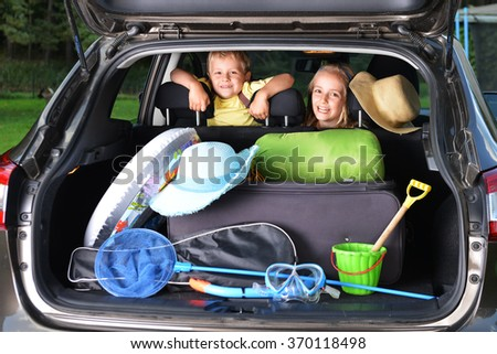little girl and her brother sitting in car  - stock photo