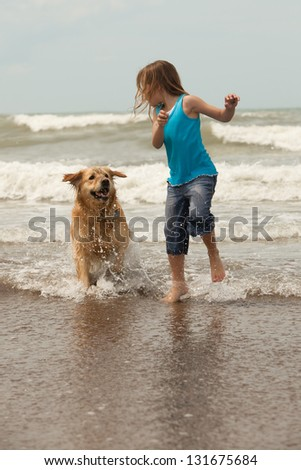 little girl and her dog running in the ocean - stock photo