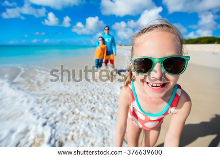 Little girl and her family father and brother enjoying beach vacation in Caribbean - stock photo