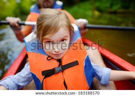 Little girl and her father on a kayak at summer - stock photo