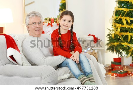 Little girl and her grandfather sitting on sofa in living room decorated for Christmas
