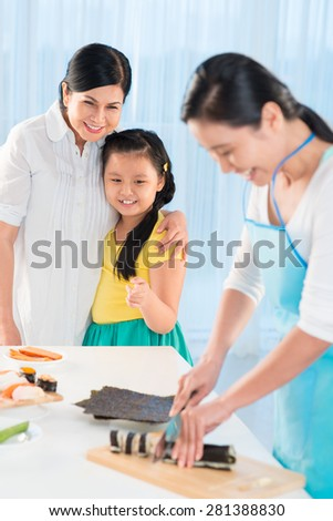 Little girl and her grandmother looking at woman cutting sushi rolls - stock photo
