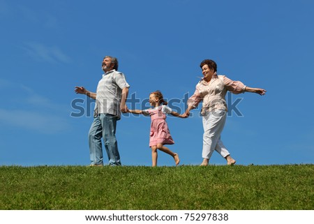 little girl and her grandparents running on lawn and holding for hands, side view