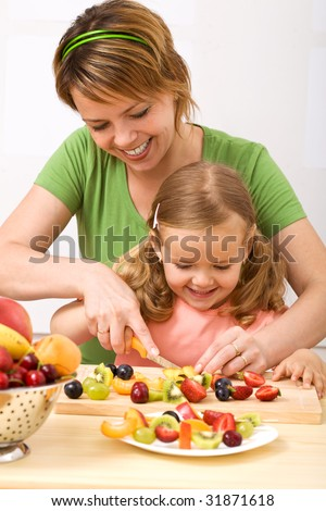 Little girl and her mom having fun preparing summer fruits salad