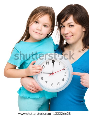 Little girl and her mother are holding a big clock, isolated over white