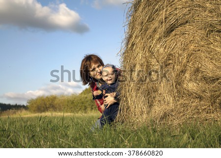 Little girl and her mother are looking out the dry haystack in the field. - stock photo