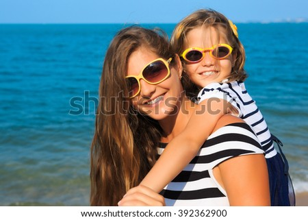 little girl and her mother have a good time at the seaside resort, on the beach - stock photo