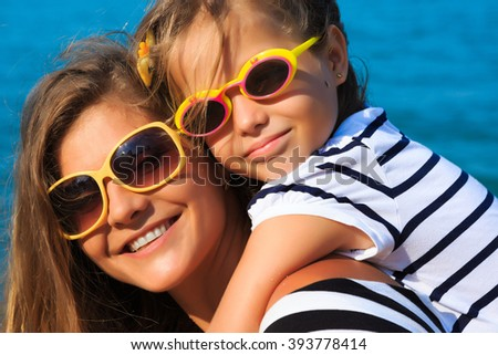 little girl and her mother have a good time at the seaside resort, on the beach