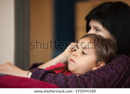 Little girl and her mother looking something interesting on TV sitting on sofa - stock photo