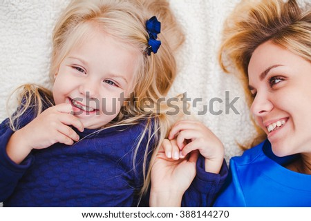 Little girl and her mother lying together on grass in summer. Family picnic. Beautiful young mom look at her cute shy daughter, both blonds in blue dresses hold hands and smile. Overhead top view - stock photo
