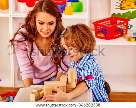 Little girl and her mother play by toy bricks at home.
