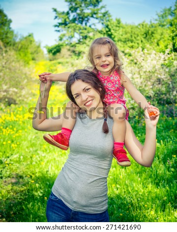 Little girl and her mother playing in the summer park - stock photo