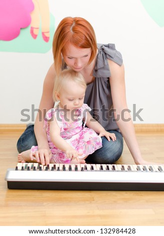 Little girl and her mother playing the piano - stock photo