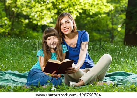 Little girl and her mother reading a book while they sitting and enjoy in beautiful nature,Mother and daughter reading a book - stock photo
