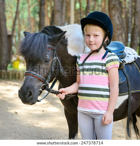Little girl and her pony - stock photo