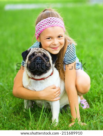 Little girl and her pug dog on green grass, outdoor shoot - stock photo