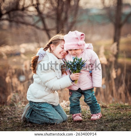 little girl and her sister holding a bouquet of snowdrops - stock photo