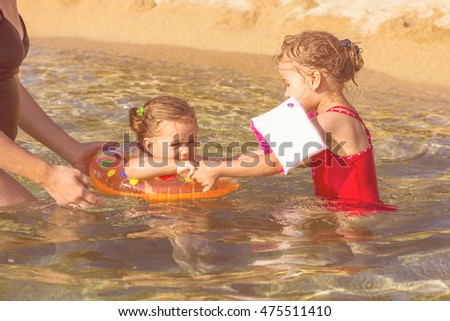 Little girl and her sister playing in the sea, Children Summer Vacation.