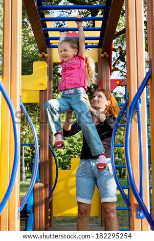 little girl and his mother at playground - stock photo