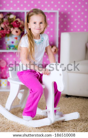 Little girl and horse - rocking chair in the bright pink polka-dot room fun game - stock photo