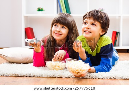 Little girl and little boy enjoy eating popcorn and watching tv at home.Leisure time for children - stock photo