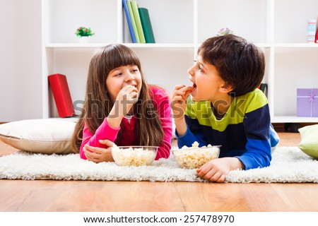 Little girl and little boy enjoy eating popcorn at home.Children eating popcorn - stock photo