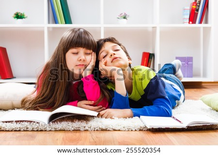 Little girl and little boy  fell asleep while they were doing their homework.We are so tired - stock photo