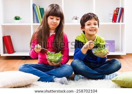 Little girl and little boy have to eat vegetables,boy is happy,but little girl is not so happy about it.One child likes to eat healthy,other doesn't like - stock photo