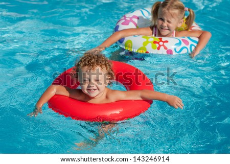 Stock photo little girl and little boy playing in the pool 143246914