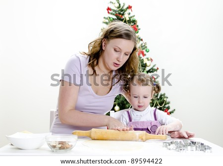 little girl and mother are preparing Christmas cookies