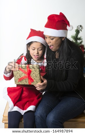 Little girl and Mother kissing and opening Christmas Present
