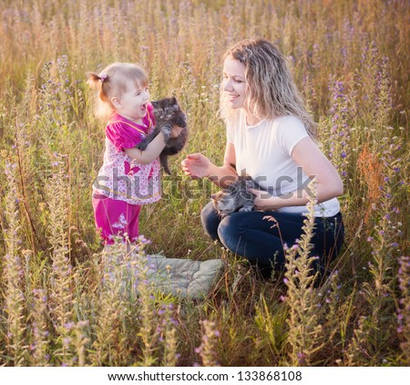 little girl and mother with cats outdoor - stock photo