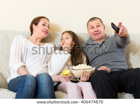 Little girl and parent sitting with popcorn in front of TV at home. Focus on girl - stock photo