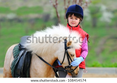 Little girl and pony - stock photo