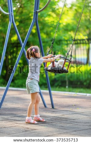 Little girl and seesaw in warm summer day