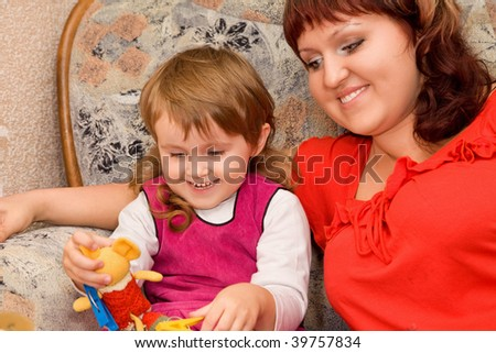 little girl and woman play a toy in a cozy room - stock photo