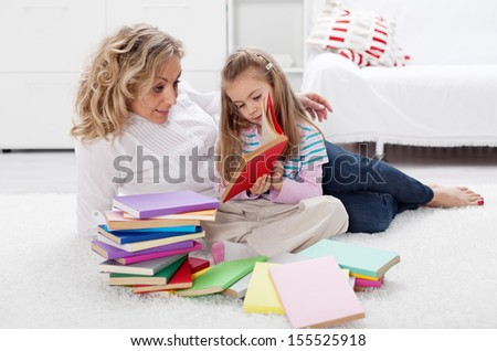 Little girl and woman reading together laying on the floor - stock photo