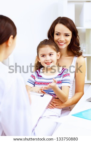 Little girl and young doctor in hospital having examination - stock photo