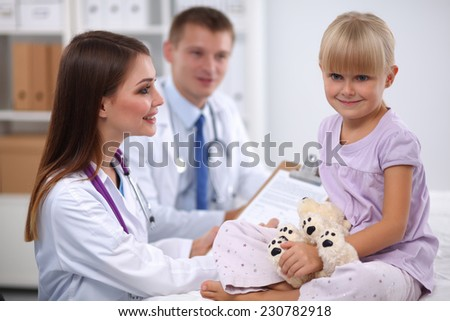 Little girl and young doctor in hospital having examination, isolated