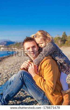 Little girl and young father at the beach have fun on a sunny winter day - stock photo