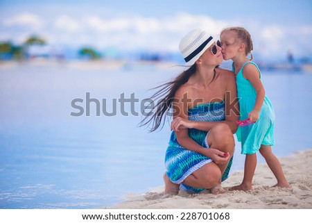 Little girl and young mother during beach vacation - stock photo