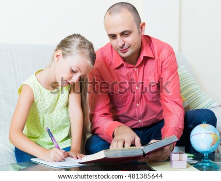 Little girl asking positive father for help with homework at home