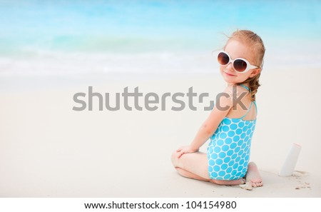 Little girl at beach with sun shaped cream at her back - stock photo