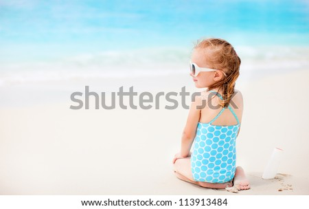 Little girl at beach with sun shaped cream at her shoulder - stock photo
