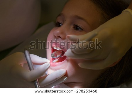 Little girl at pediatric dentists office, being examined by her dentist. Early prevention, oral hygiene and milk teeth care concept.   - stock photo