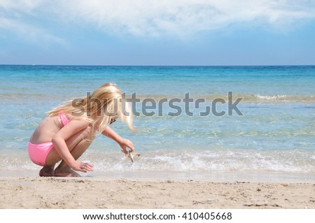 Little girl at the beach playing with starfish. Summer vacation concept - stock photo