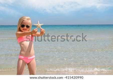 Little girl at the beach playing with starfish. Summer vacation concept