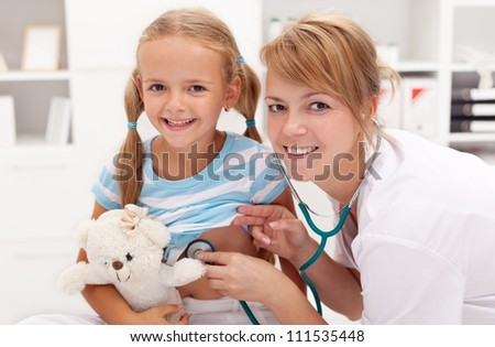 Little girl at the doctor's - pediatric checkup - stock photo
