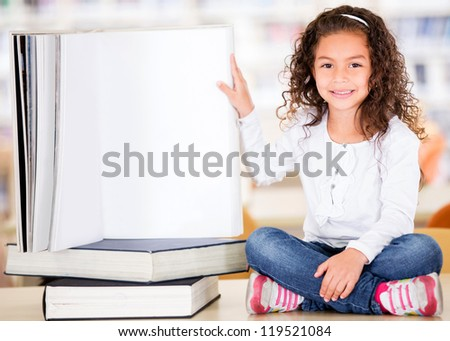 Little girl at the library with a big book - stock photo