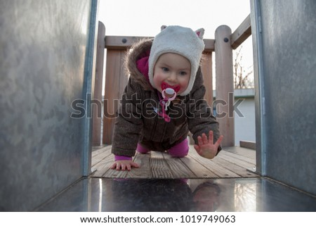 little girl at the playground playing on a slide